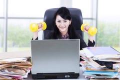 Γυναίκα που εργάζεται και workout στο γραφείο 1 Στοκ Φωτογραφίες
