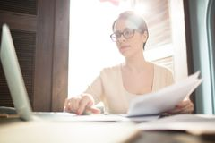 Γυναίκα που εργάζεται με τα έγγραφα και το lap-top Στοκ Φωτογραφία