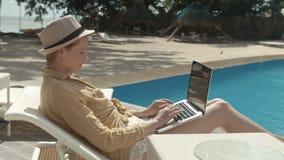 Γυναίκα που εργάζεται με τον υπολογιστή στις διακοπές στο θέρετρο πολυτέλειας απόθεμα βίντεο