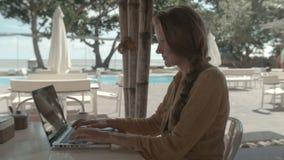 Γυναίκα που εργάζεται με τον υπολογιστή στις διακοπές στο θέρετρο πολυτέλειας φιλμ μικρού μήκους