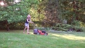 Γυναίκα που εργάζεται στην τέμνουσα χλόη κήπων με το θεριστή χορτοταπήτων 4K απόθεμα βίντεο