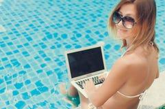Γυναίκα που εργάζεται στη συνεδρίαση φορητών προσωπικών υπολογιστών της στο poolside στοκ εικόνες