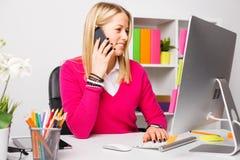 Γυναίκα που εργάζεται στον υπολογιστή και που μιλά στο τηλέφωνο Στοκ Εικόνες