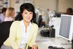 Γυναίκα που εργάζεται στο γραφείο στο απασχολημένο δημιουργικό γραφείο Στοκ εικόνες με δικαίωμα ελεύθερης χρήσης