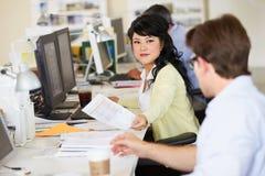 Γυναίκα που εργάζεται στο γραφείο στο απασχολημένο δημιουργικό γραφείο Στοκ φωτογραφία με δικαίωμα ελεύθερης χρήσης