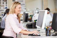 Γυναίκα που εργάζεται στο γραφείο στο απασχολημένο δημιουργικό γραφείο Στοκ φωτογραφίες με δικαίωμα ελεύθερης χρήσης