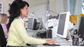 Γυναίκα που εργάζεται στο γραφείο στο απασχολημένο δημιουργικό γραφείο φιλμ μικρού μήκους