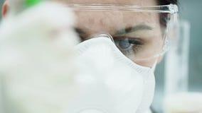 Γυναίκα που εργάζεται στο εργαστήριο με τα αντιδραστήρια στο σωλήνα απόθεμα βίντεο