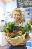 Γυναίκα που εργάζεται στο κατάστημα με το καλάθι των φρέσκων προϊόντων Στοκ εικόνες με δικαίωμα ελεύθερης χρήσης
