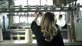 Γυναίκα που εργάζεται στο νήμα που ξανατυλίγει το βίντεο μηχανών απόθεμα βίντεο