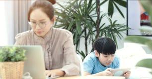 Γυναίκα που εργάζεται στο lap-top με τον υπολογιστή ταμπλετών παιχνιδιού αγοριών στοκ εικόνες