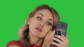 Γυναίκα που εφαρμόζει μαύρο mascara στα eyelashes που κοιτάζουν στο τηλέφωνό της σε μια πράσινη οθόνη, κλειδί χρώματος φιλμ μικρού μήκους