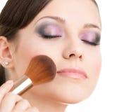 Γυναίκα που εφαρμόζει τα καλλυντικά στο πρόσωπό της στοκ φωτογραφία με δικαίωμα ελεύθερης χρήσης