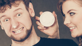 Γυναίκα που εφαρμόζει την κρέμα στο πρόσωπο ανδρών της Στοκ φωτογραφία με δικαίωμα ελεύθερης χρήσης