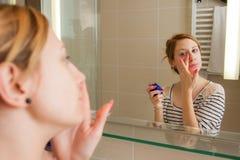 Γυναίκα που εφαρμόζει την κρέμα στο πρόσωπο στοκ εικόνες με δικαίωμα ελεύθερης χρήσης