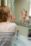 Γυναίκα που εφαρμόζει την κρέμα στο πρόσωπο στοκ φωτογραφίες