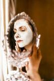 Γυναίκα που εφαρμόζει τη μάσκα του δέρματος αργίλου στο πρόσωπο που κοιτάζει στον καθρέφτη στοκ φωτογραφία