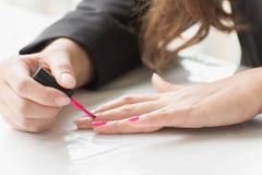 Γυναίκα που εφαρμόζει τη ρόδινη στιλβωτική ουσία καρφιών σε διαθεσιμότητα Στοκ φωτογραφίες με δικαίωμα ελεύθερης χρήσης