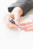 Γυναίκα που εφαρμόζει τη ρόδινη στιλβωτική ουσία καρφιών σε διαθεσιμότητα Στοκ Εικόνα