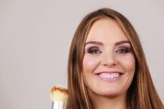 Γυναίκα που εφαρμόζει τη χαλαρή σκόνη με τη βούρτσα στο πρόσωπό της Στοκ Φωτογραφία