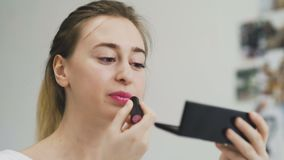 Γυναίκα που εφαρμόζει το κραγιόν στα χείλια της μπροστά από τον καθρέφτη απόθεμα βίντεο