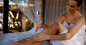 Γυναίκα που εφαρμόζει το λοσιόν καθμένος στο κρεβάτι θόλων 4k απόθεμα βίντεο