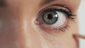 Γυναίκα που εφαρμόζει mascara στα μακροχρόνια eyelashes της κοντά επάνω φιλμ μικρού μήκους
