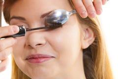 Γυναίκα που εφαρμόζει mascara που χρησιμοποιεί το κουτάλι στοκ εικόνες