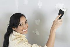 Γυναίκα που εφαρμόζει Putty στον τοίχο στοκ εικόνες