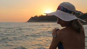 Γυναίκα που εφαρμόζει sunscreen στον ώμο της θερμό σε έναν κοντινό η λαμπιρίζοντας θάλασσα φιλμ μικρού μήκους