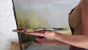 Γυναίκα που δημιουργεί τη ζωγραφική με τα ελαιοχρώματα και τη βούρτσα, στενό UPS απόθεμα βίντεο