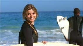 Γυναίκα που θέτει ενώ φίλος που τρέχει στο νερό απόθεμα βίντεο