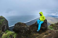 Γυναίκα που θέτει στον απότομο βράχο Dyrholaey, Ισλανδία Στοκ φωτογραφίες με δικαίωμα ελεύθερης χρήσης