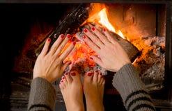 Γυναίκα που θερμαίνει τα πόδια χεριών της ands Στοκ εικόνα με δικαίωμα ελεύθερης χρήσης