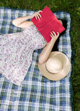 Γυναίκα που διαβάζει ένα βιβλίο έξω στη χλόη στοκ εικόνες