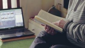 Γυναίκα που διαβάζει ένα βιβλίο στο σπίτι κοντά στο lap-top φιλμ μικρού μήκους