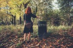 Γυναίκα που διαθέτει τα απορρίματα στο δάσος Στοκ Φωτογραφίες