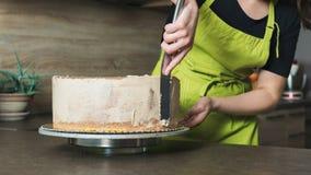 Γυναίκα που διακοσμεί ένα εύγευστο βαλμένο σε στρώσεις κέικ σφουγγαριών με την κρέμα τήξης σοκολάτας Στοκ Φωτογραφίες