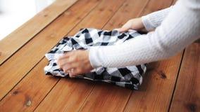Γυναίκα που διπλώνει το ελεγμένο πουκάμισο στον πίνακα στο σπίτι φιλμ μικρού μήκους