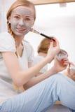 Γυναίκα που ισχύει με τη μάσκα λάσπης αργίλου βουρτσών για το πρόσωπό της Στοκ Εικόνες