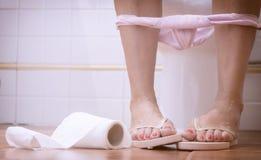 Γυναίκα που κάθεται στην τουαλέτα στοκ εικόνες