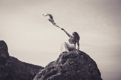 Γυναίκα που κάθεται όμορφη πάνω από το μαντίλι εκμετάλλευσης απότομων βράχων που τυλίγει στοκ εικόνες