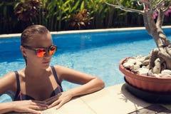 Γυναίκα που κάνει ηλιοθεραπεία στην πισίνα στοκ εικόνα