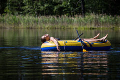 Γυναίκα που κάνει ηλιοθεραπεία σε μια βάρκα Στοκ Εικόνα