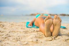 Γυναίκα που κάνει ηλιοθεραπεία στην άμμο Στοκ Εικόνες