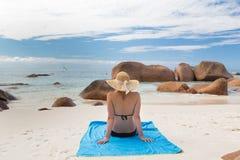 Γυναίκα που κάνει ηλιοθεραπεία στην τέλεια παραλία εικόνων Anse Λάτσιο στο νησί Praslin, Σεϋχέλλες Στοκ Φωτογραφίες