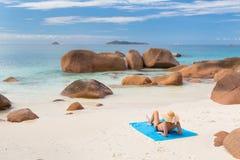 Γυναίκα που κάνει ηλιοθεραπεία στην τέλεια παραλία εικόνων Anse Λάτσιο στο νησί Praslin, Σεϋχέλλες Στοκ Εικόνα