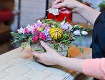 Γυναίκα που κάνει μια ανθοδέσμη των τριαντάφυλλων σε ένα καλάθι Στοκ Εικόνες