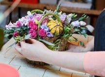 Γυναίκα που κάνει μια ανθοδέσμη των τριαντάφυλλων σε ένα καλάθι Στοκ φωτογραφία με δικαίωμα ελεύθερης χρήσης