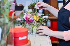 Γυναίκα που κάνει μια ανθοδέσμη των τριαντάφυλλων σε ένα καλάθι Στοκ Φωτογραφία